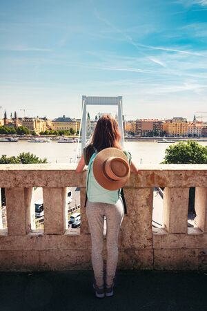 Rear view of young woman with backpack and hat, traveling in the Budapest city, Hungary.
