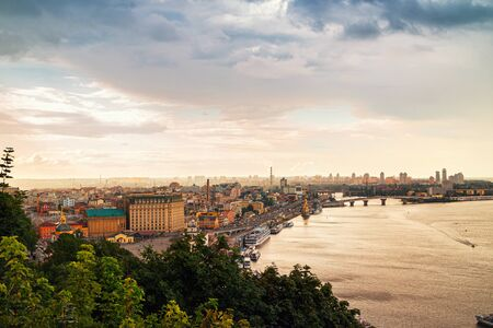 View from above to the Kyiv city and Dnipro river, Ukraine. cloudy sky before rain with warm sunset light.