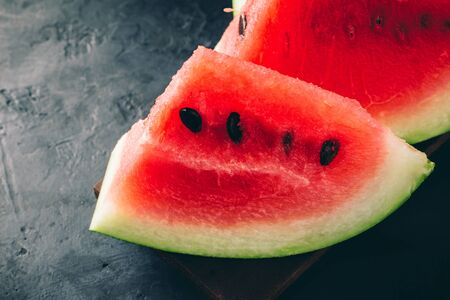 Ripe red watermelon pieces, close up view on dark background.