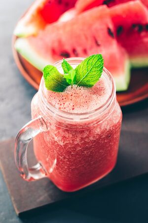 Watermelon red smoothie in jar with fresh mint leaves on dark background.