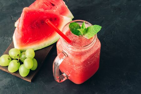 Watermelon red smoothie in jar with fresh mint leaves and grape on dark background.