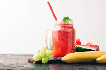 Watermelon red smoothie in jar with fresh mint leaves, banana and grape.