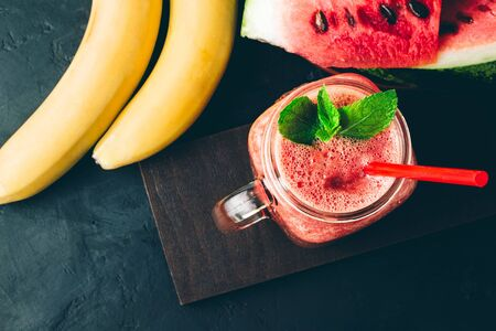 Watermelon red smoothie in jar with banana and fresh mint leaves on dark background, top view.