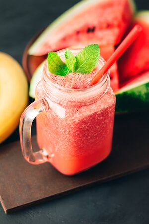 Watermelon red smoothie in jar with banana and fresh mint leaves on dark background.