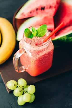 Watermelon red smoothie in jar with fresh mint leaves, banana and grape on dark background.
