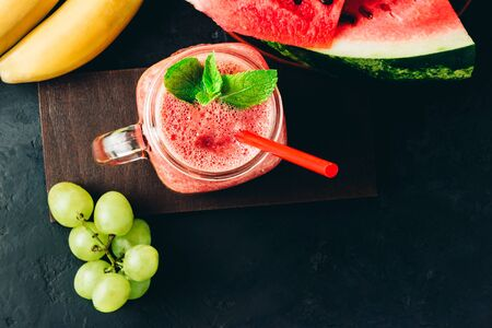 Watermelon red smoothie in jar with fresh mint leaves, banana and grape on dark background, top view.