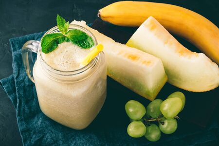 Melon smoothie in a jar with fresh mint leaves, banana and grape on dark background. Stockfoto
