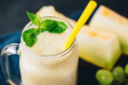 Melon smoothie in a jar with fresh mint leaves and grape on dark background.