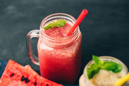 Smoothie from watermelon and melon in a jars with fresh mint leaves, grape on dark background. Stock fotó