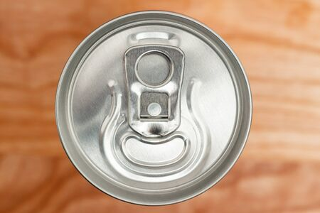 unopened aluminium can with soda drink or beer on wooden background, top view.