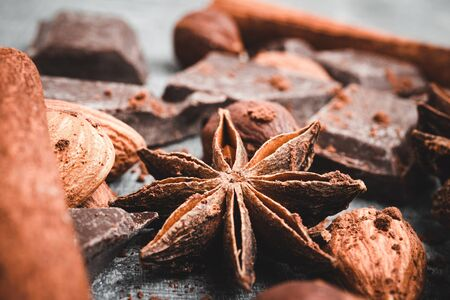 Star anise, chocolate cubes and nuts, close-up view.