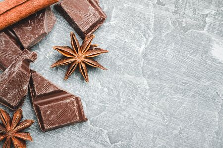 Chocolate cubes, star anise and cinnamon stick on grey textured background, top view.