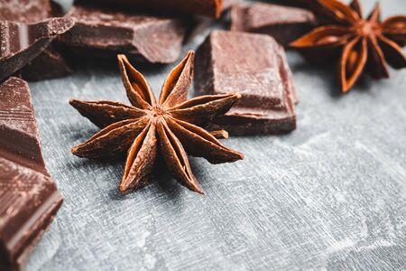 Star anise and chocolate cubes on grey textured background, close-up view.