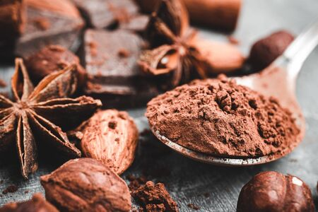 Brown cocoa powder in the spoon, chocolates, star anise and nuts, close-up view, selective focus. Stock Photo