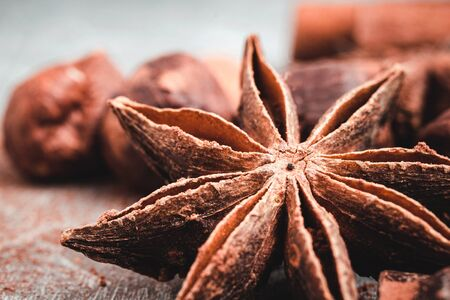 Star anise, chocolate cubes and nuts on grey textured background, close-up view. Stock Photo