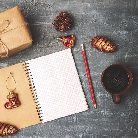 Empty paper in notepad for your text, with gift box, pencil, coffee cup and decoration, New Year and Christmas concept, top view. Stock fotó