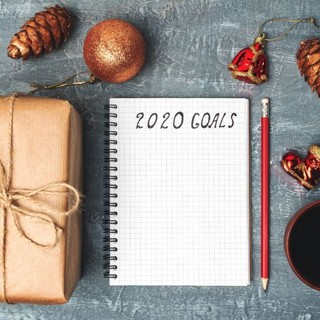 2020 goals, text on the paper in notepad, New Year promises concept, gift box, coffee cup, decorations, top view.