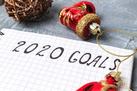 2020 goals, text on the paper in notepad, close up view New Year promises concept.