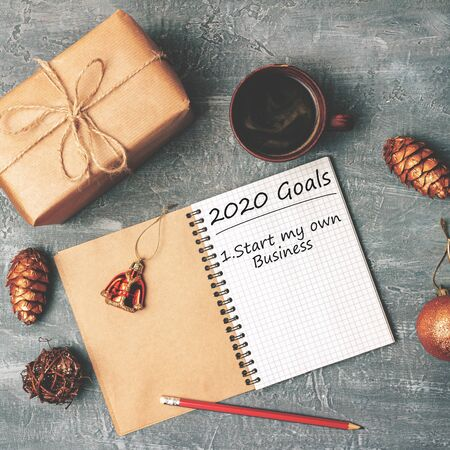 2020 goals, start own business, text on the paper in notepad, New Year promises concept, gift box, coffee cup, decorations, top view.