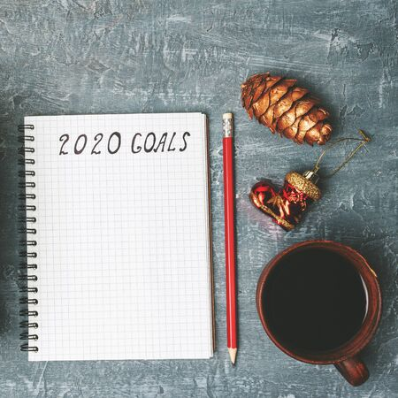 2020 goals, text on the paper in notepad, New Year promises concept, pencil, coffee cup, decorations, top view.