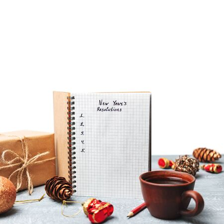New Years resolution, text on the paper in notepad, promises concept, gift box, pencil, coffee cup, isolated on white.