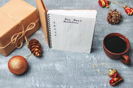 New Years resolution, text on the paper in notepad, promises concept, gift box, pencil, coffee cup, decorations. Stock fotó
