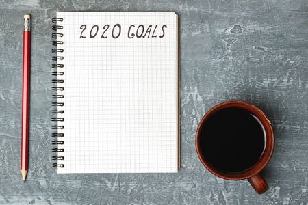2020 goals, text on the paper in notepad, New Year promises concept, pencil, coffee cup, top view. Stock fotó