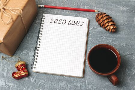 2020 goals, text on the paper in notepad, New Year promises concept, gift box, coffee cup, decorations. Stock fotó