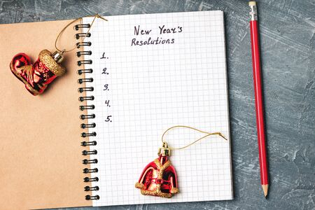 New Years resolution, text in notepad, promises concept, pencil, decorations on dark background, top view. Stock fotó