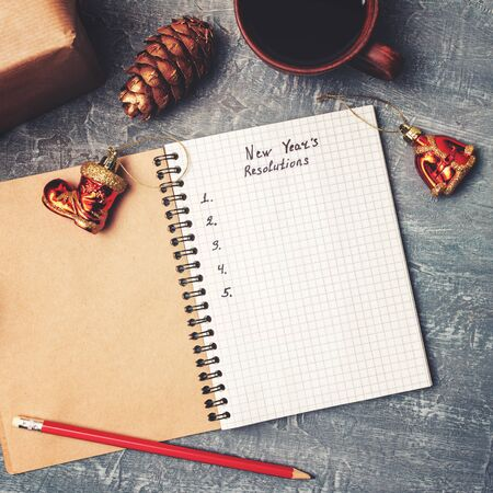 New Years resolution, text in notepad, promises concept, pencil, coffee cup, decorations, top view.