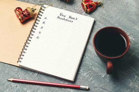 New Years resolution, text on the paper in notepad, promises concept, pencil, coffee cup, decorations. Stock fotó