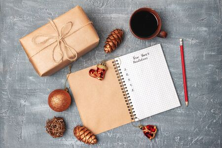 New Years resolution, text in notepad, promises concept, gift box, coffee cup, decorations, top view.