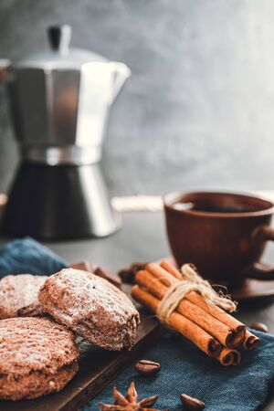 Chocolate cookies, cup with coffee, moka pot, cinnamon sticks, star anise on blue napkin, dark background with copy space.