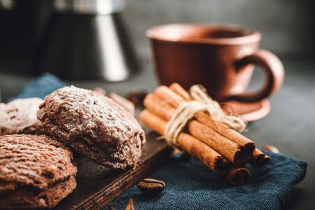 Homemade bakery, chocolate cookies with powdered sugar, cinnamon sticks and cup with coffee, close-up view.