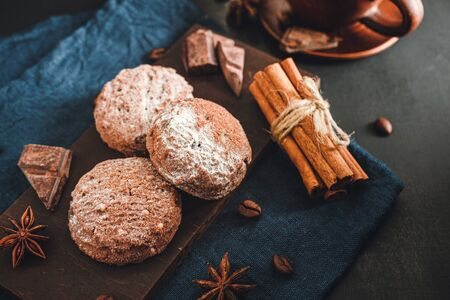 Homemade bakery, chocolate cookies with powdered sugar, cinnamon sticks, star anise on blue napkin, dark background. Stock fotó