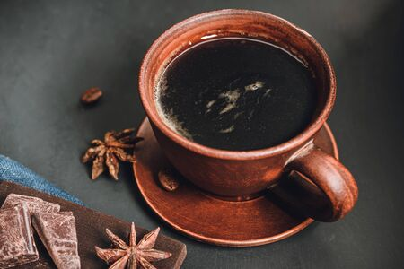 Brown cup with black coffee, chocolate pieces, star anise on dark background. Stock fotó
