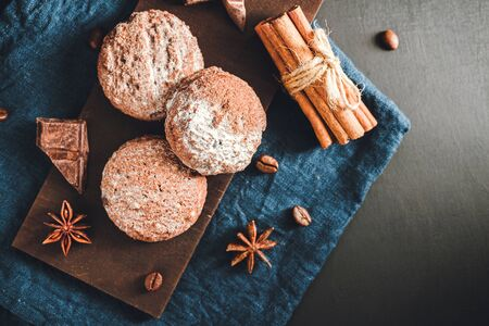 Homemade bakery, chocolate cookies with powdered sugar, cinnamon sticks, star anise on blue napkin, top view. Banco de Imagens - 134745569