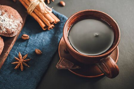 Brown cup with black coffee, cookies, cinnamon sticks, star anise on dark background.