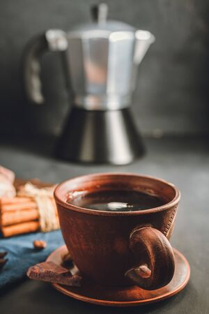 Brown cup with black coffee, cinnamon sticks, moka pot on dark background.