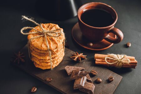 Homemade cookies and brown cup with coffee on dark background.