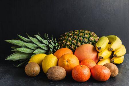 Assortment of tropical fruits, banana, kiwi, orange, tangerine, lemon, pineapple, grapefruit on dark background, copy-space.