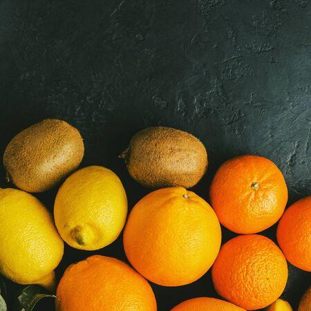 Assortment of tropical fruits, banana, kiwi, orange, tangerine, lemon, grapefruit on dark background, top view, copy-space.
