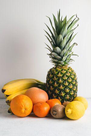 Assortment of tropical fruits, banana, kiwi, orange, tangerine, lemon, pineapple, grapefruit on textured white background. 写真素材