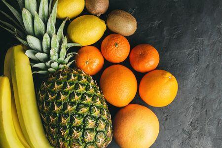 Assortment of tropical fruits, banana, kiwi, orange, tangerine, lemon, pineapple, grapefruit on dark background, top view, copy-space.