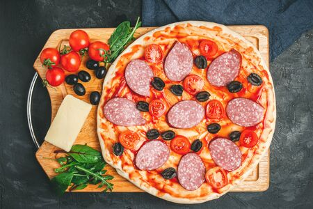 Process of making pizza round dough with black olives, cherry tomatoes, mozzarella cheese, sliced salami and green leaves spinach, rucola, top view. Stock Photo