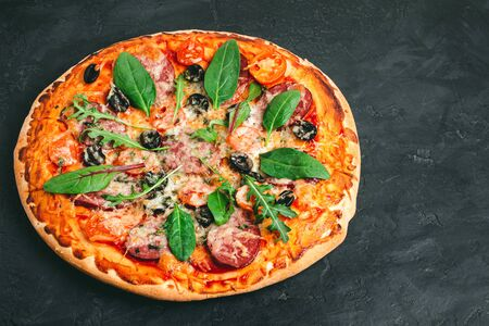 Homemade baked pizza margarita with salami, mozzarella cheese, olives and green leaves. Stockfoto