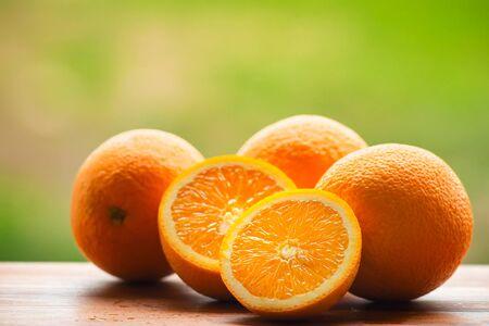 Orange fruits on wooden board, at blurred nature background.