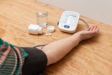 Woman has hypertension, measuring blood pressure on the hand with digital tonometer, hypertensive drugs, treatment pills and water glass on table.