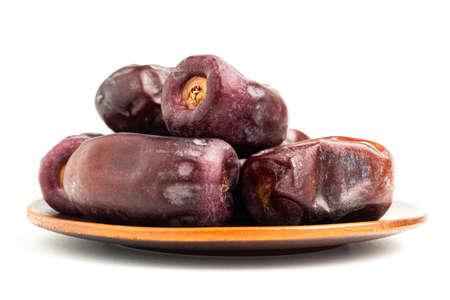 Dried organic date fruits in a plate, isolated on white background.