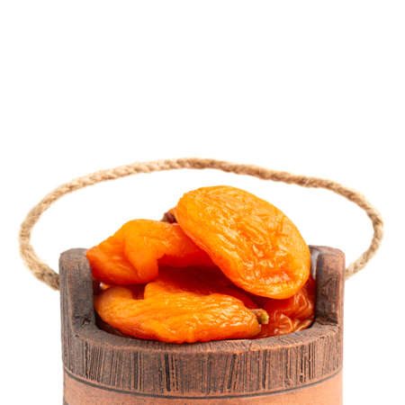 Dried apricots fruit in a bowl, isolated on white background, close up view.